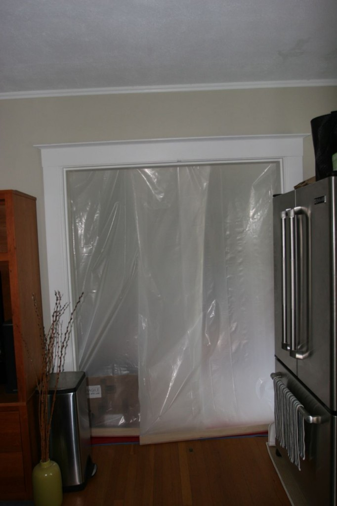 """I realized I hadn't posted anything of our current """"kitchen."""" Through that plastic door is the foyer."""