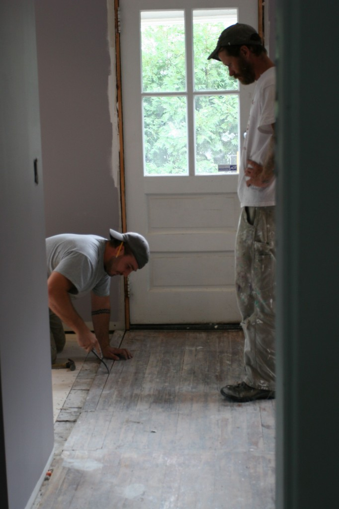 Dave gently removing the antique boards while Eric watches.