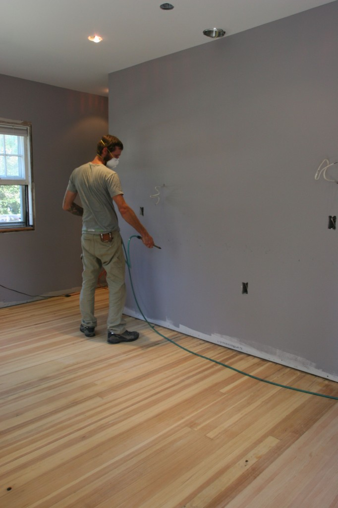 Eric using the compressor to blow all the fine dust away off the walls and floor.