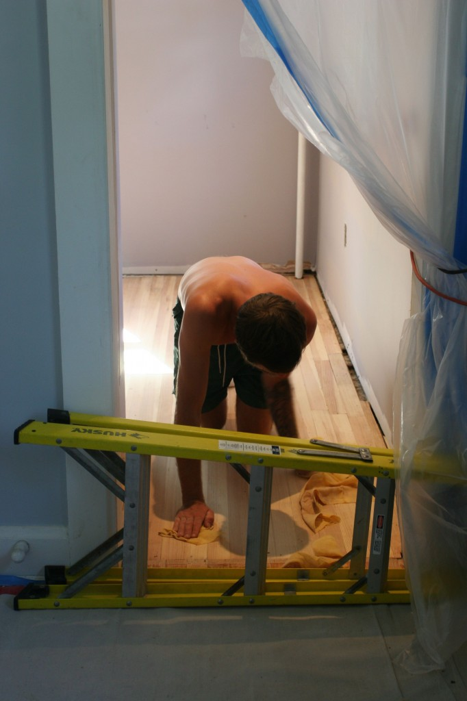 Eric behind our make-shift baby(dog) gate wiping all the residual dust from the floors.