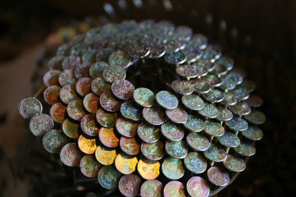 Roofing nails in a lovely, scale-like, iridescent spiral. They had no idea that these nails were so pretty.