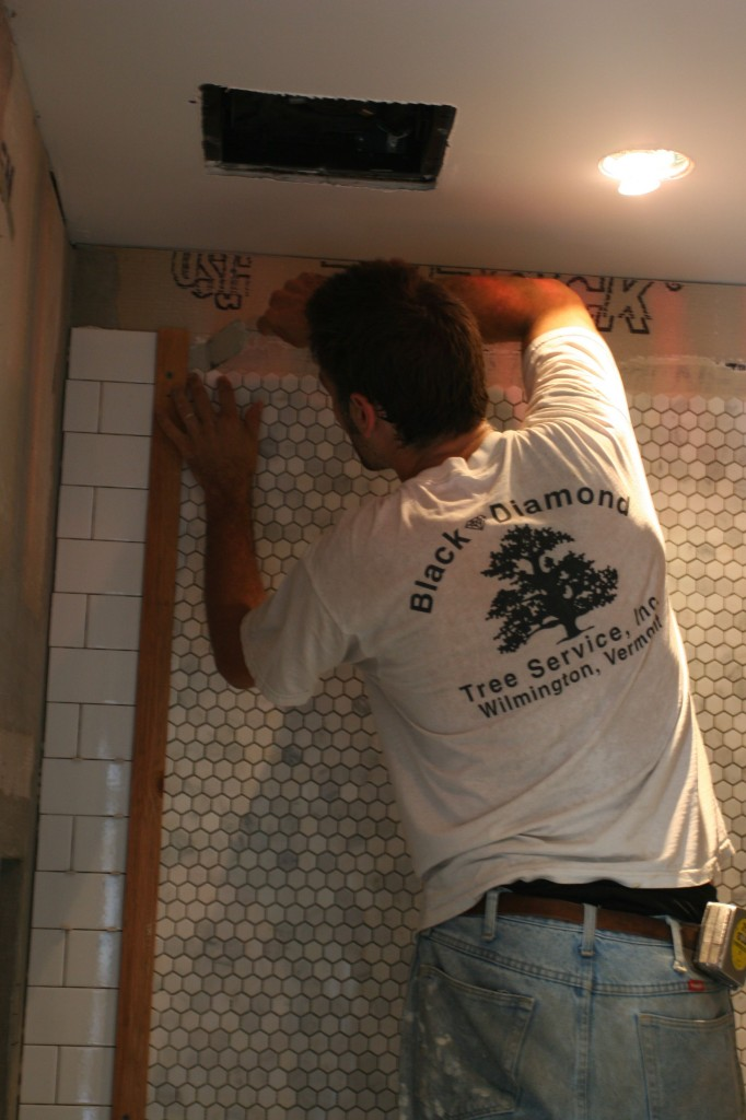 Carefully scraping back the excess thin-set so tomorrow's tile can be applied to a fresh, smooth wall.