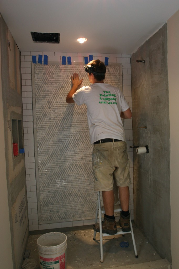 """J.J. checking for """"loose tooth"""" tiles that might not have adhered fully when they were pressed into place. Even though these are put up in sheets, they each have to be touched to ensure proper placement. Yikes."""