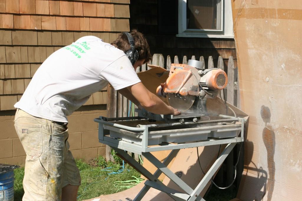 J.J. working the tile saw outside. Melting.