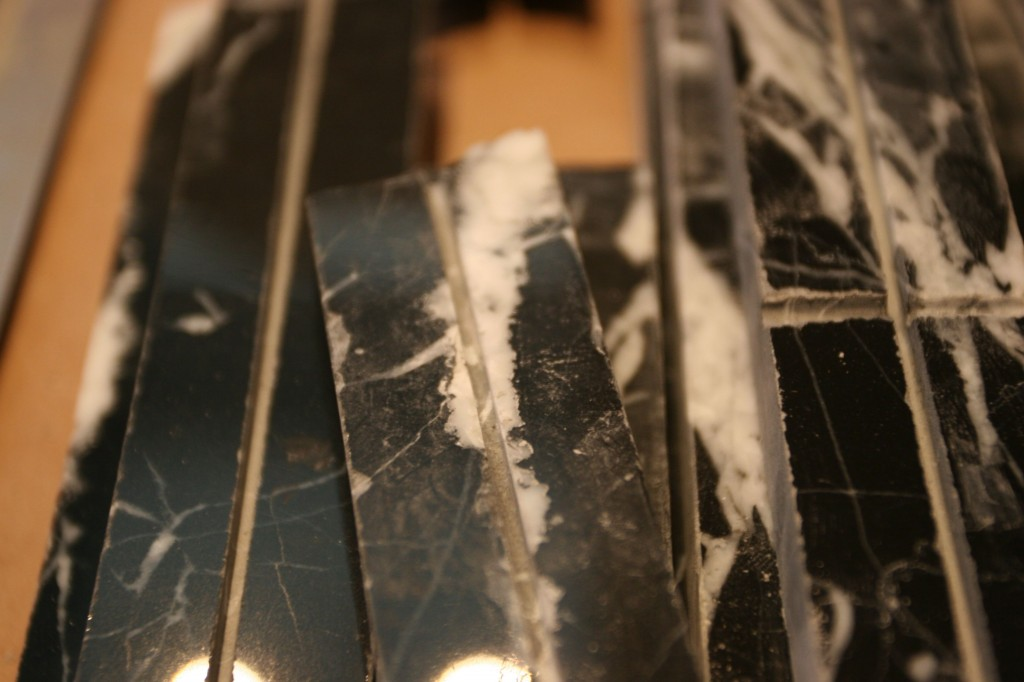 """Caleb and J.J. ripped 12"""" square black marble pieces into 1"""" pieces with grooves routed into them. This will make them LOOK like they are smaller pieces (6"""" and under) when we grout it, but give the strength and flatness of a whole piece. Genius. Freaking genius."""