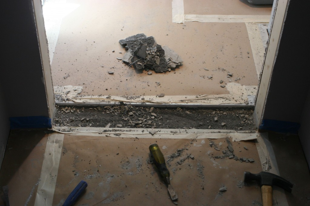 Caleb was using just about every tool he could find to carefully chisel out the underlayment to make space for the threshold.