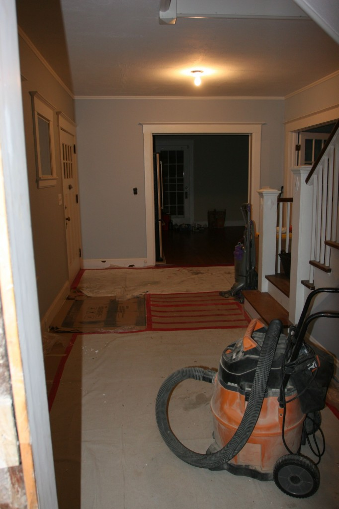The foyer, empty but for a few mostly empty boxes, the shop-vac and some cardboard.