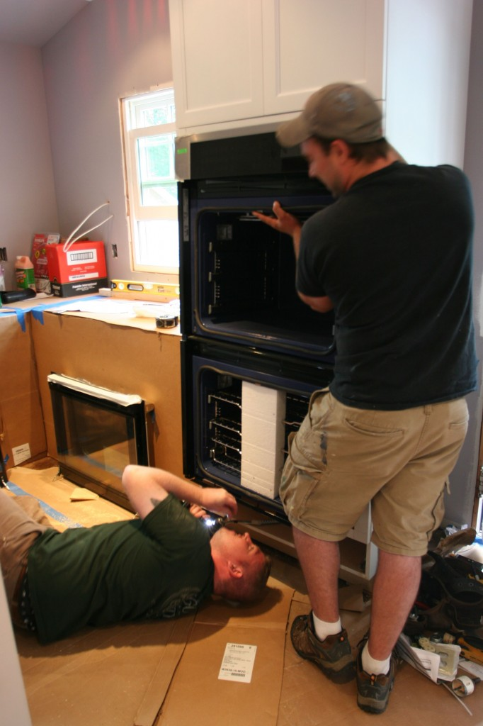Brad in his favorite spot - the floor - installing the safety bracket for the wall ovens while Dave held the 200+ lb. appliance by himself.