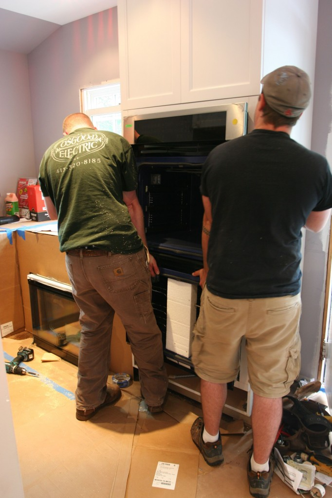 Adjusting the ovens into place. (The guys look mighty good here, right?)