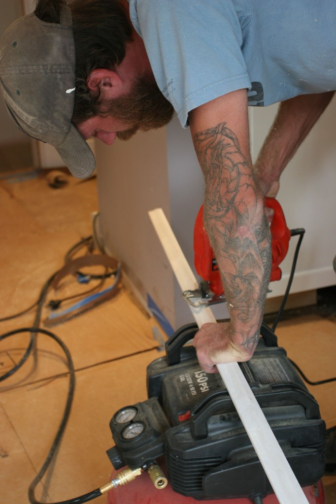 Eric jigsawing some baseboard trim to allow for the powder room water supply.