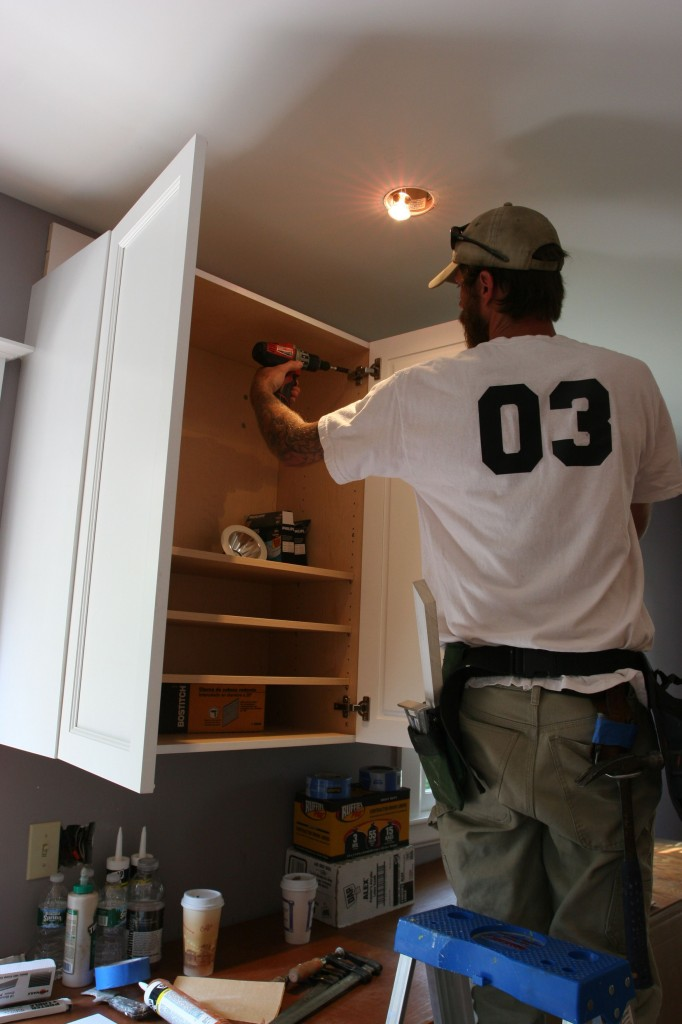Eric adjusting the doors to make them sit level with the top of the cabinet.