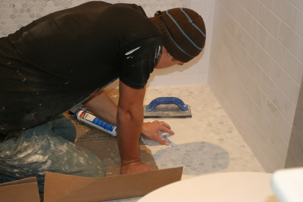 J.J. finishing up the shower drain (hidden underneath the grout).