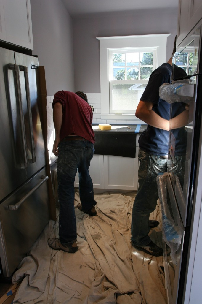 "The boys grouting away. (THEY started singing ""Let's get it grouted in here"" a la The Black Eyed Peas. They, not me.)"