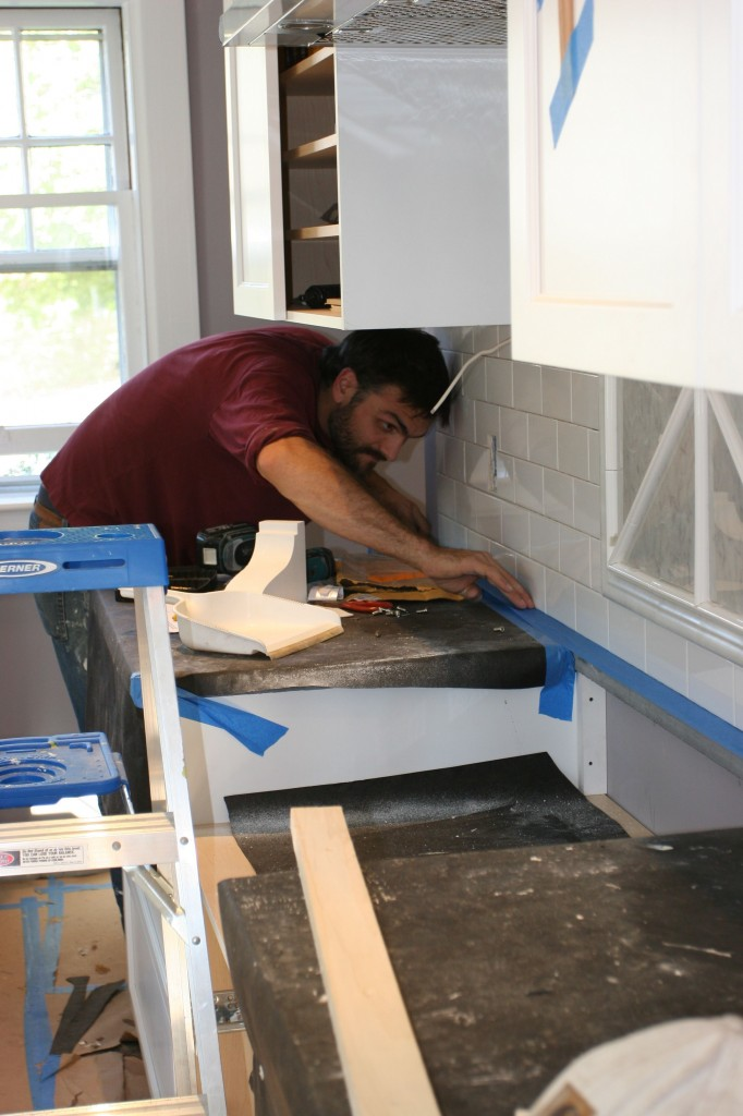 Caleb laying down some blue tape to protect our countertops from errant grout (or sealer, later).