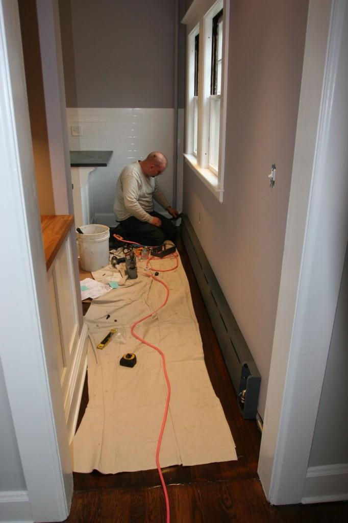 Matt (Team Plumbing) installing the baseboard steam radiator.