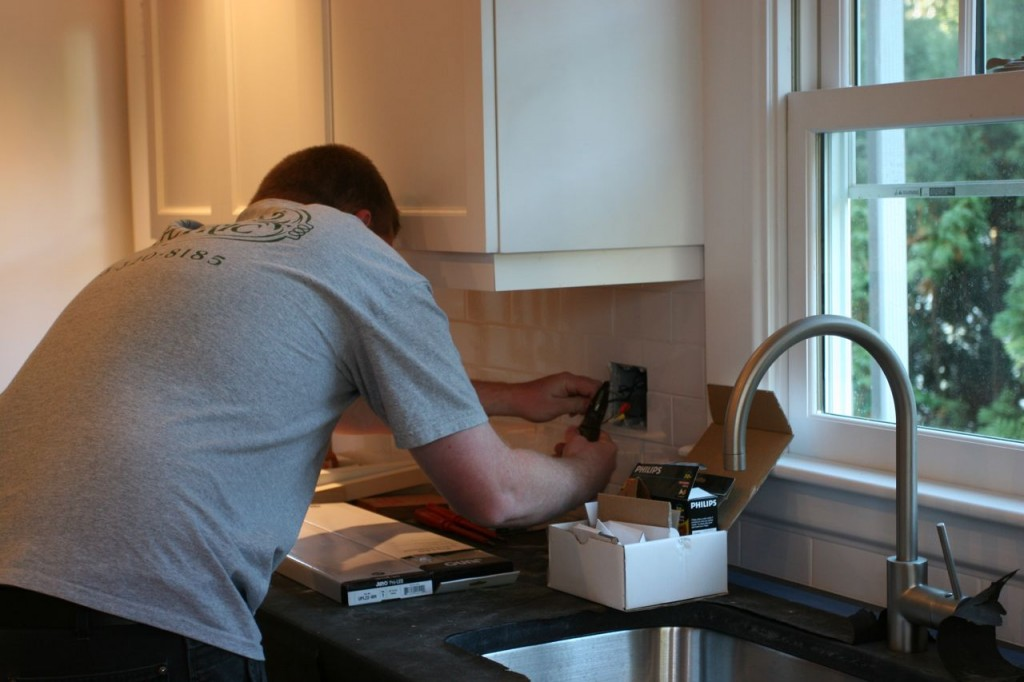 Brad wrangling the kitchen sink switch. We have light!