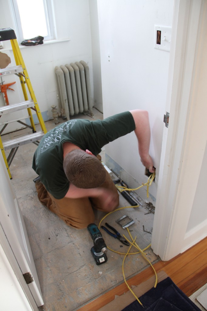 Brad snaking the wires for the electric floor mat to the bottom of the wall.