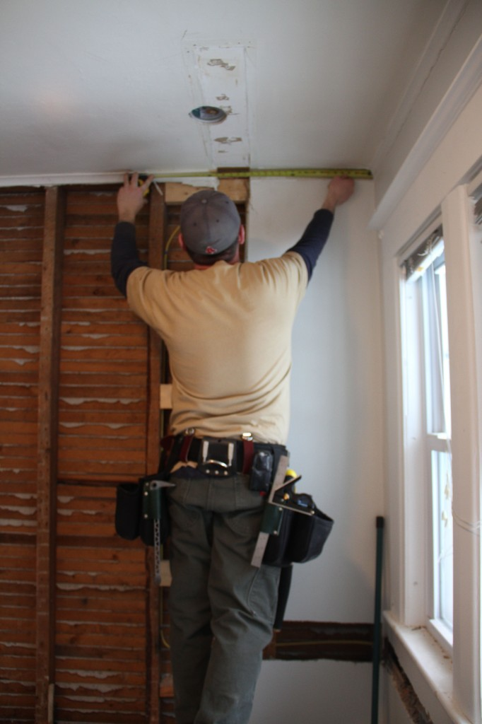 "Jonas measuring a bit of crown molding they saved from the aforementioned ""stupid wall."" Waste not, want not!"