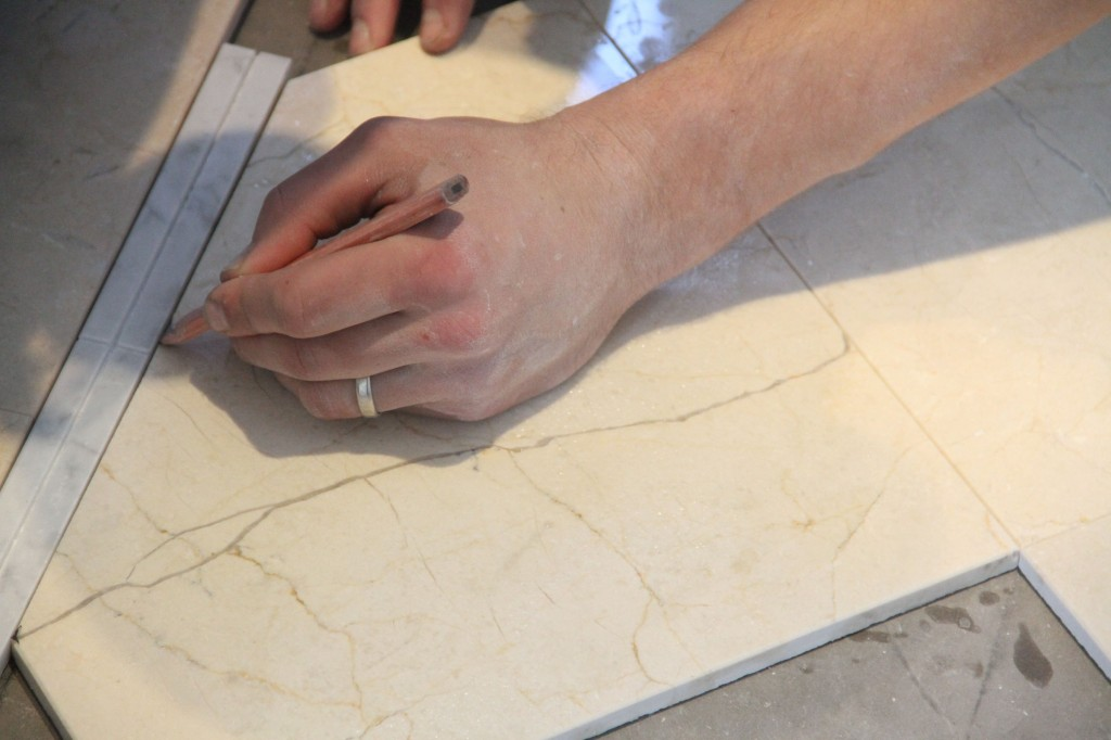 Marking the spots that needed trimming to keep the grout lines the same all around the room. This takes mad skills, people. Or should I say skillz.