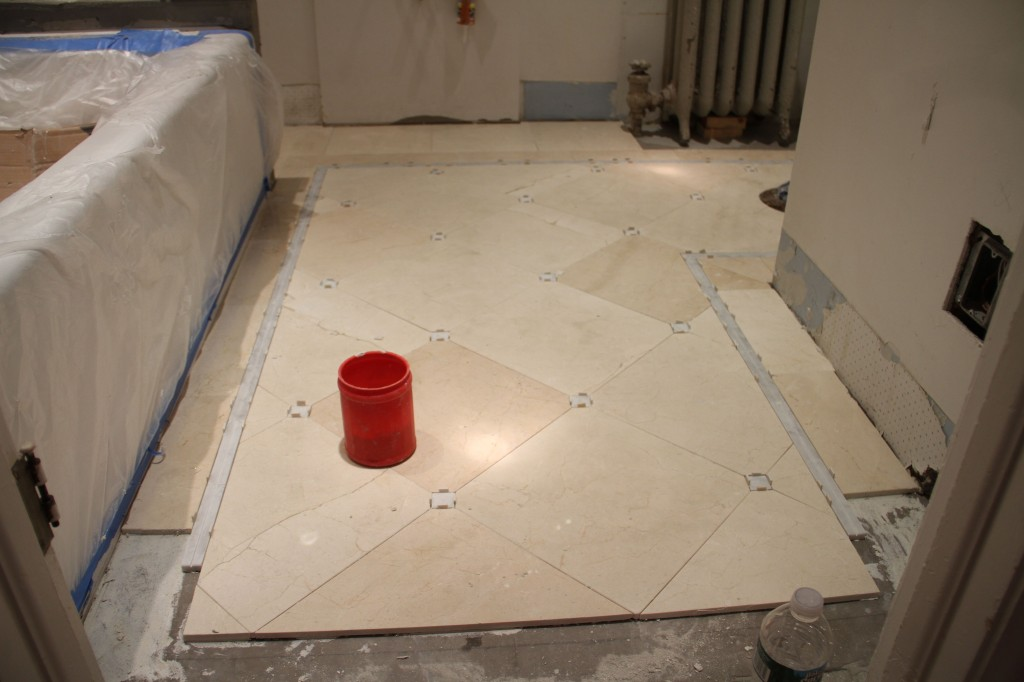The last bits of the floor have to go in AFTER the threshold piece. But for now, we can protect the floor and walk on it. Woo hoo!