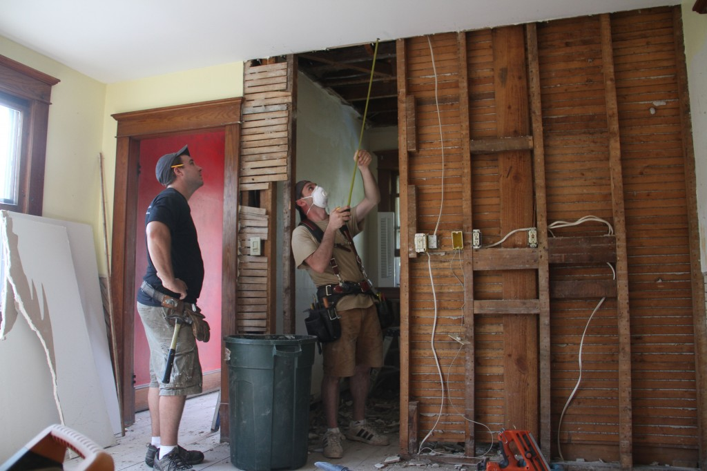 Dave and Jonas measuring the difference between ceiling heights in the adjacent spaces (formerly separated by a door).
