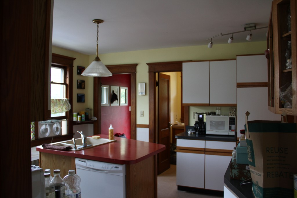 BEFORE: south wall. Dated pendants, make-it-work lighting fixtures, rickety cabinetry and awkward space planning made these homeowners decide to put the kitchen out of its misery.