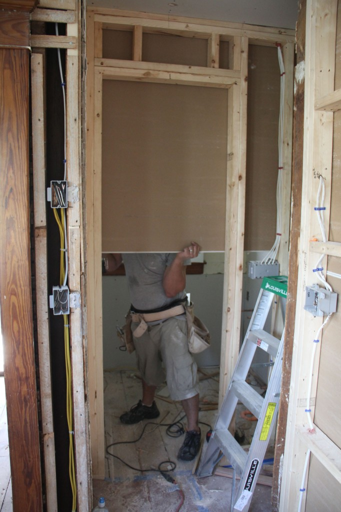 Brian affixing the 'rock to the inside of the bathroom.