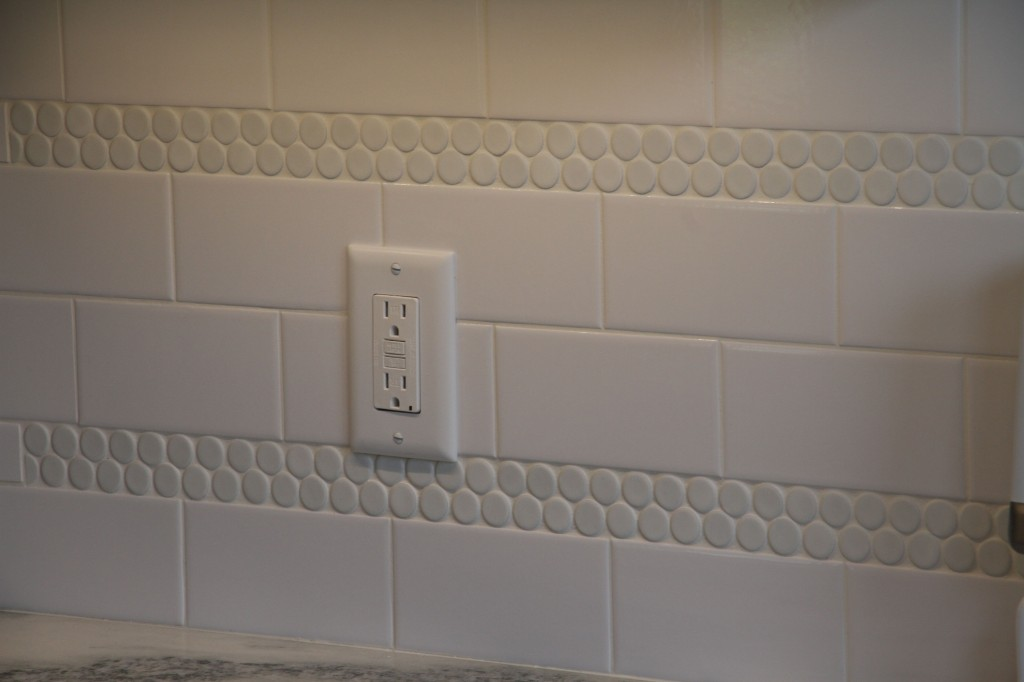I never did get to snap any pictures of JJ and Caleb tiling the backsplash. Here it is, with a couple of accent rows of penny tile to pick up on the penny tile in the adjacent powder room.