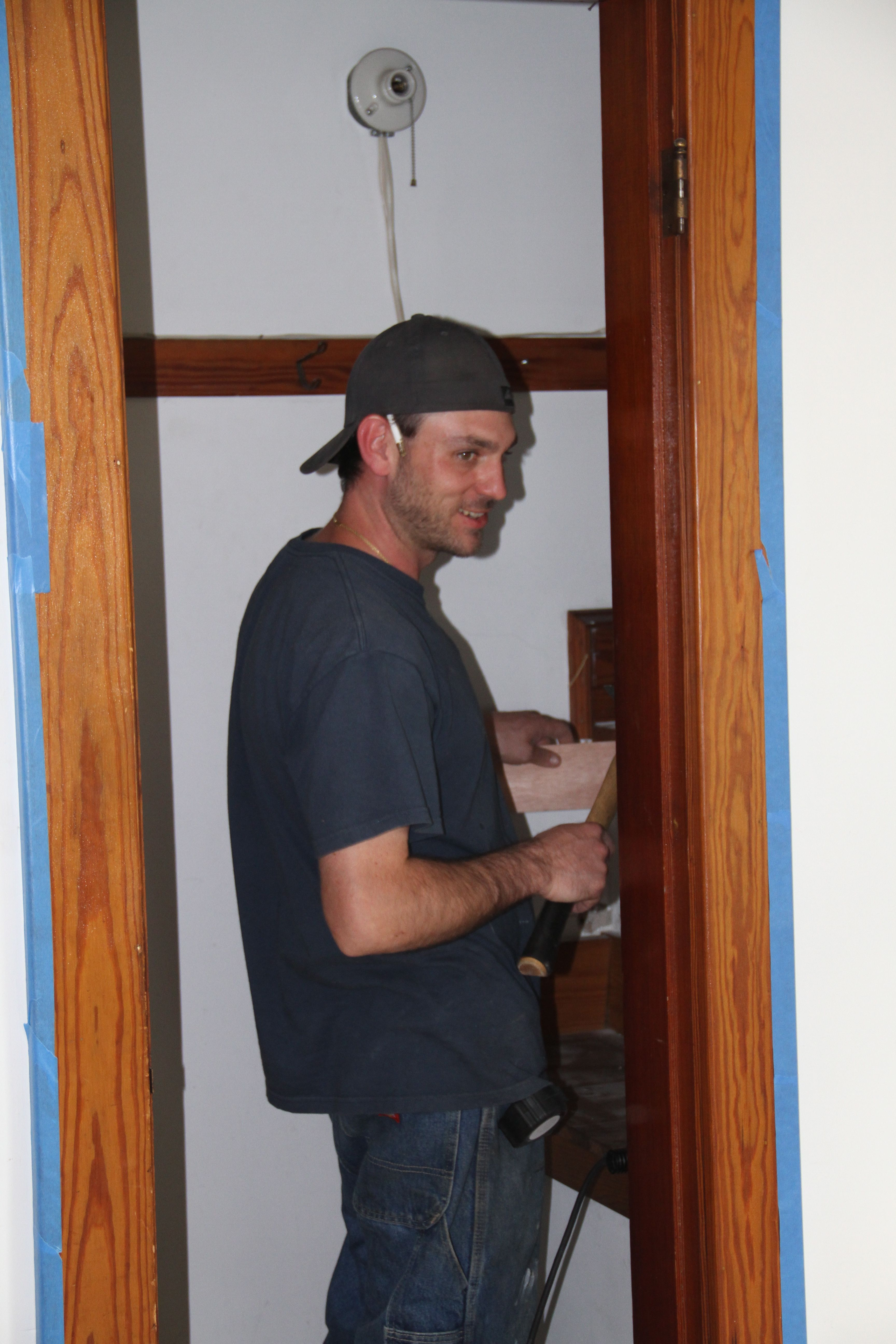 Jonas, in a rare smiling shot, poaching some wood from the closet for a minor adjustment in the kitchen.