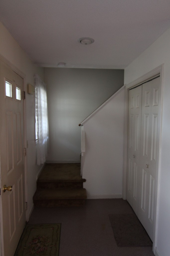 The entryway BEFORE: grungy, carpet and linoleum, needing a bit of paint and love.