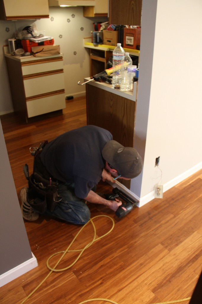 Jonas working the finish nail gun. Unlike the former nails that were all throughout the baseboards, the nails Jonas used were small, and of correct proportion for the job they were doing.