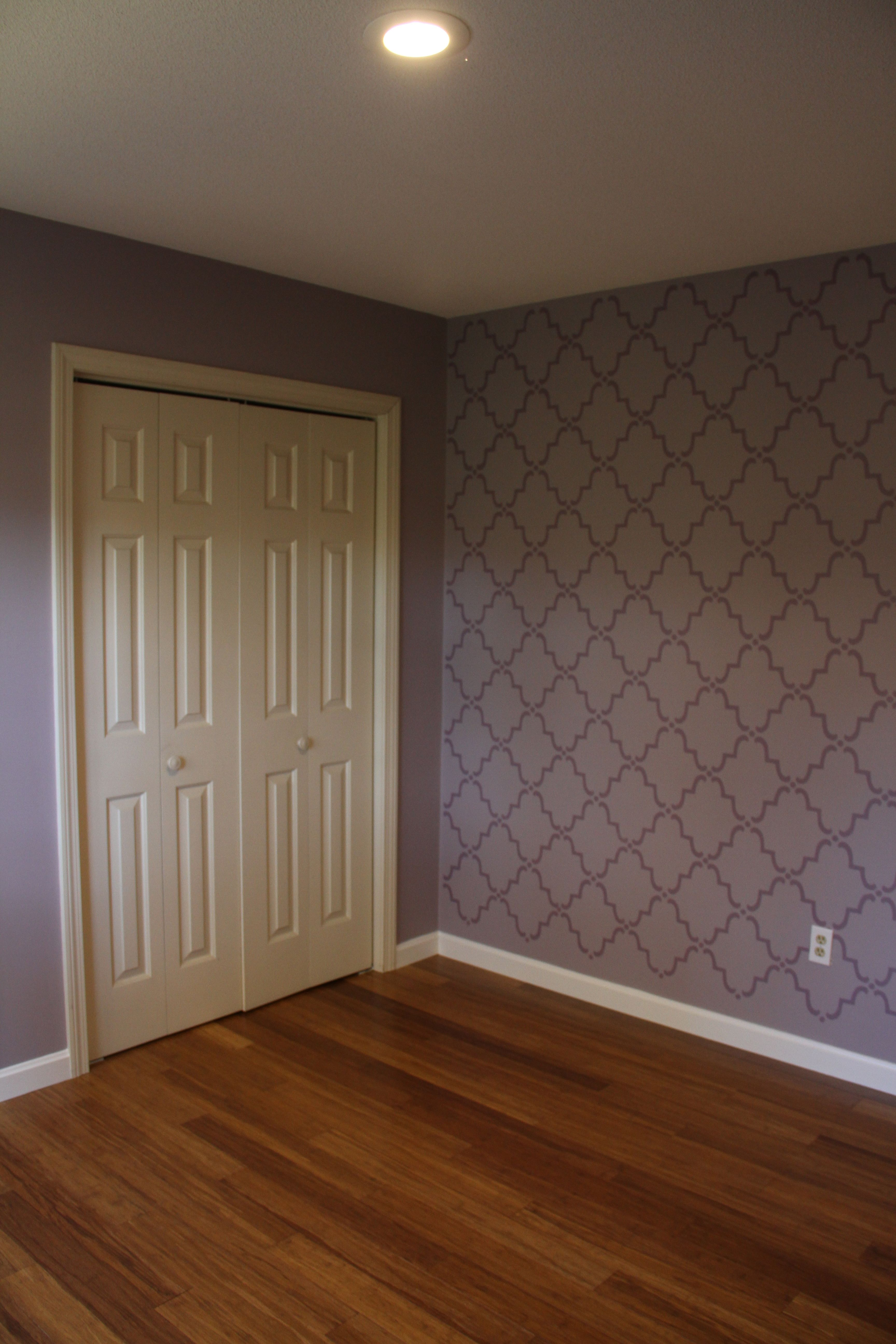 AFTER: Master bedroom. Mom loved the stencil. I loved it much better with the finished baseboard and new flooring. Not too shabby.