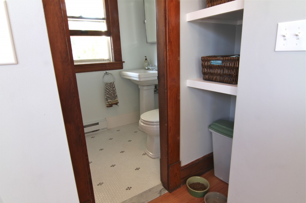 AFTER: The Ks chose penny tile for the flooring and a classic pedestal sink to pay respect to the historic features of their home. And, that formerly un-captured kitchen space was turned into a versatile pantry area that can house anything from extra food and drink, to doggie supplies.