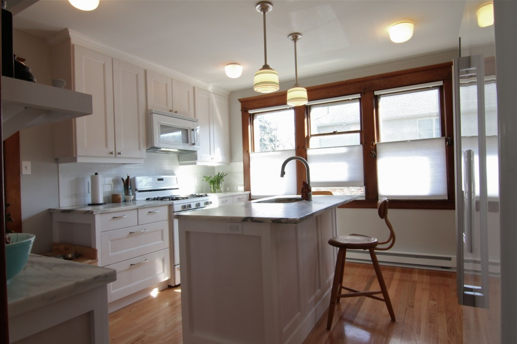 AFTER: Reorienting the sink to face the back of the kitchen, moving the placement of the refrigerator, updating the heating, and organizing the seating in usable areas, the kitchen now feels functional and open.