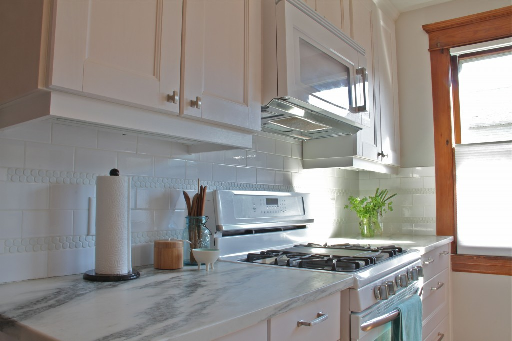 AFTER: Now the light floods the space, and the prep areas are nearly 3' wide. Plus, the built-in microwave hood is an efficient solution for small kitchens.