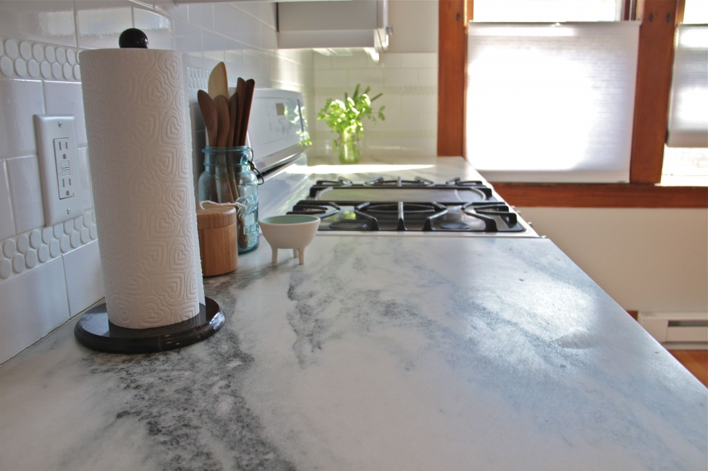 AFTER: The countertops have lovely movement, deep grays to pale whites, and brighten the space considerably. Plus, that charcoal grey tone is picked up in the powder room penny tile accents, as well as the soft grey color on the walls.