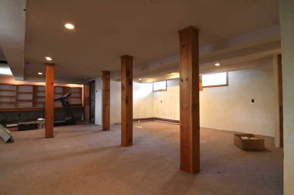 Basement BEFORE: knotty pine, shabby (not chic) carpet, dingy paint, peeling wallpaper.