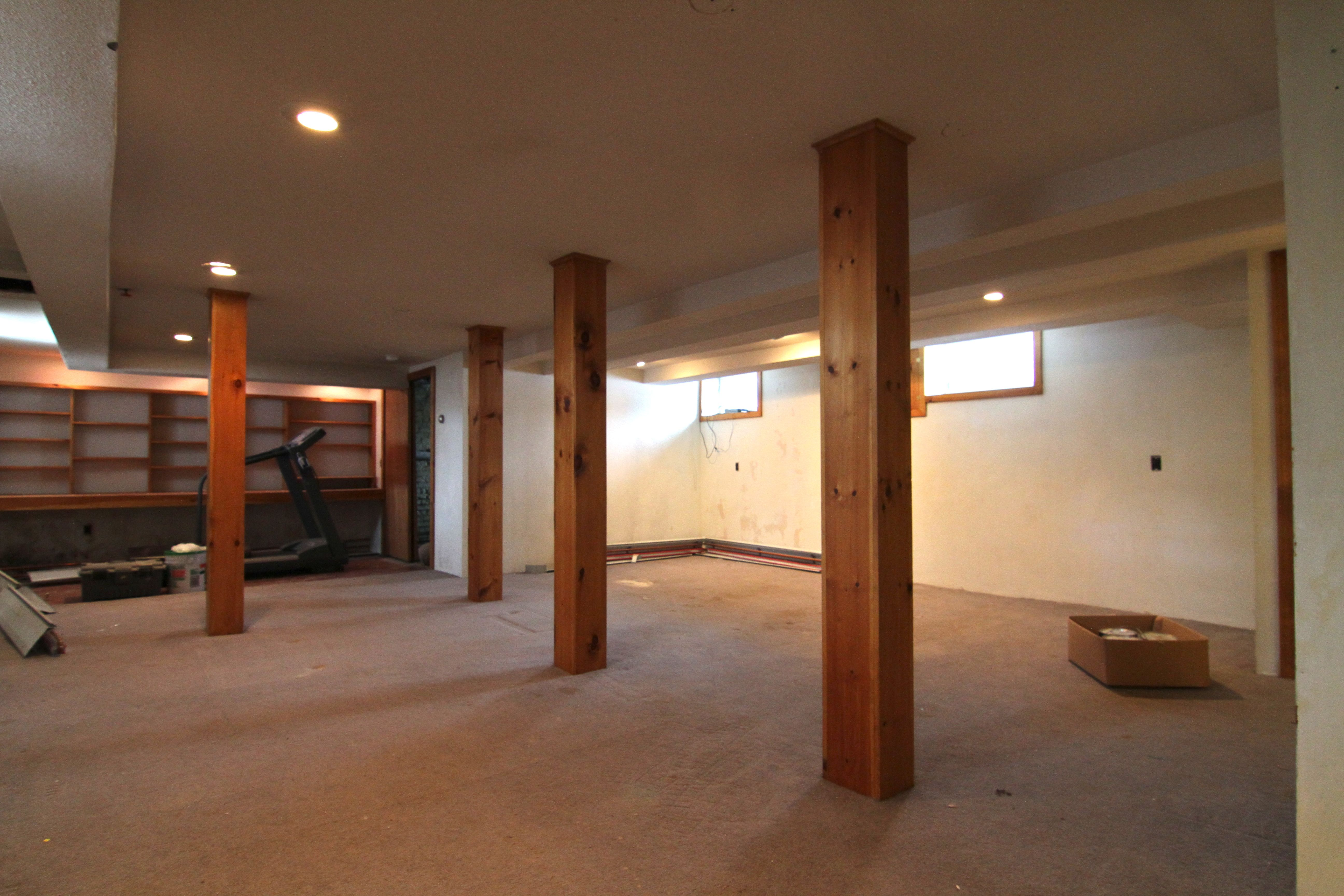 Basement BEFORE: knotty pine, shabby (not chic) carpet, dingy paint, peeling wallpaper.