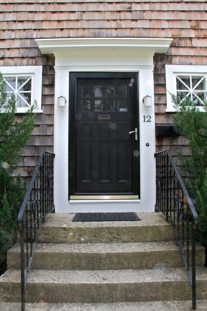 AFTER: The front door, with its storm door in place. The old one was broken, dingy, and white. This one lets you know that the extra-wide, original front door is black, glossy, and full of details.