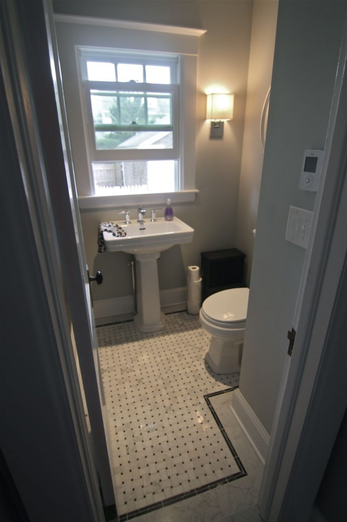 Powder room on the main level features a new window, water-saving toilet, marble floors and radiant electric floor heat.