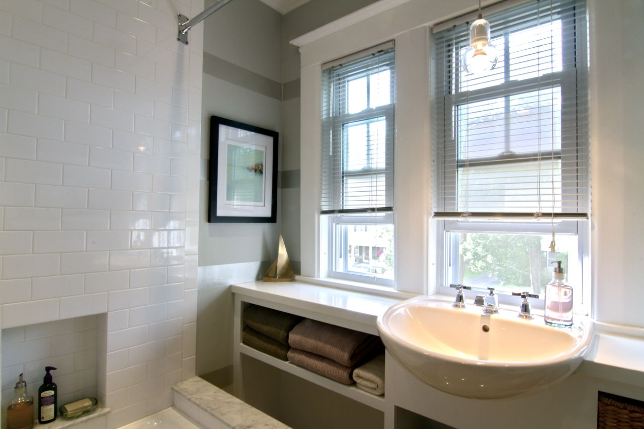 Family bath, upstairs, featuring custom wall cabinet, new sink, faucet, cast iron bathtub, toilet and marble flooring with electric radiant floor heat.