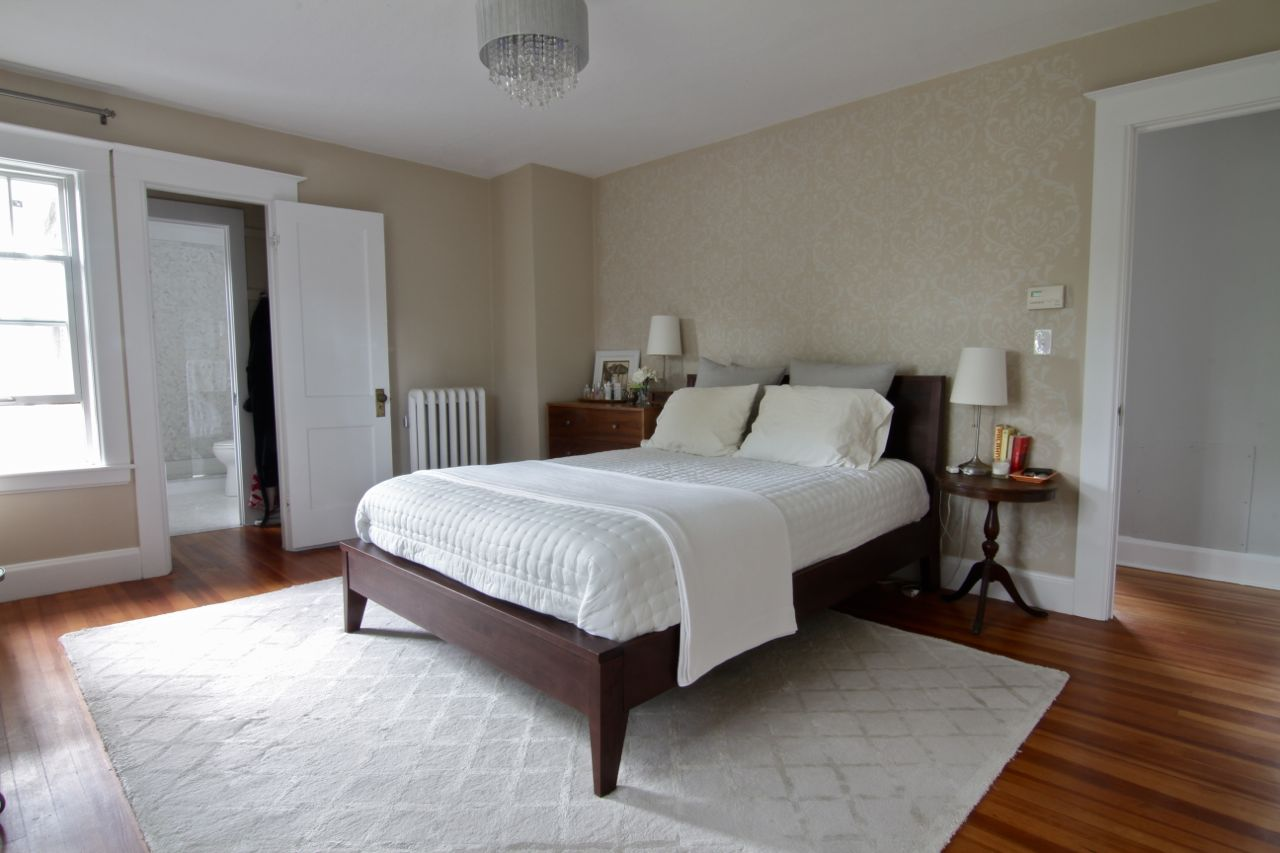 Master bedroom, featuring adjacent en suite bathroom, new ceiling fixture, faux paint accent wall, two closets and original fir floors.