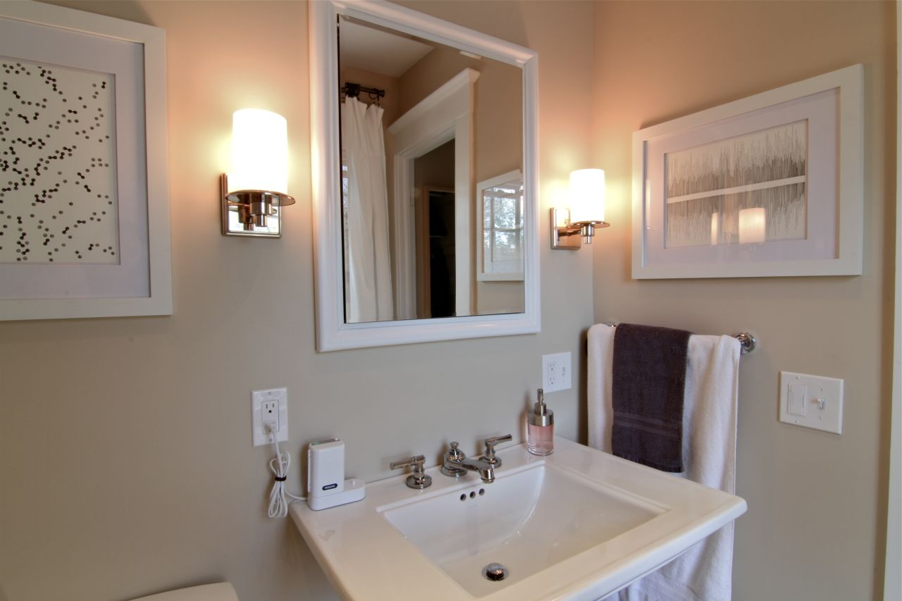 Sconces, on a dimmer, provide adequate lighting for make-up application or shaving, while the recessed medicine cabinet provides plenty of storage.