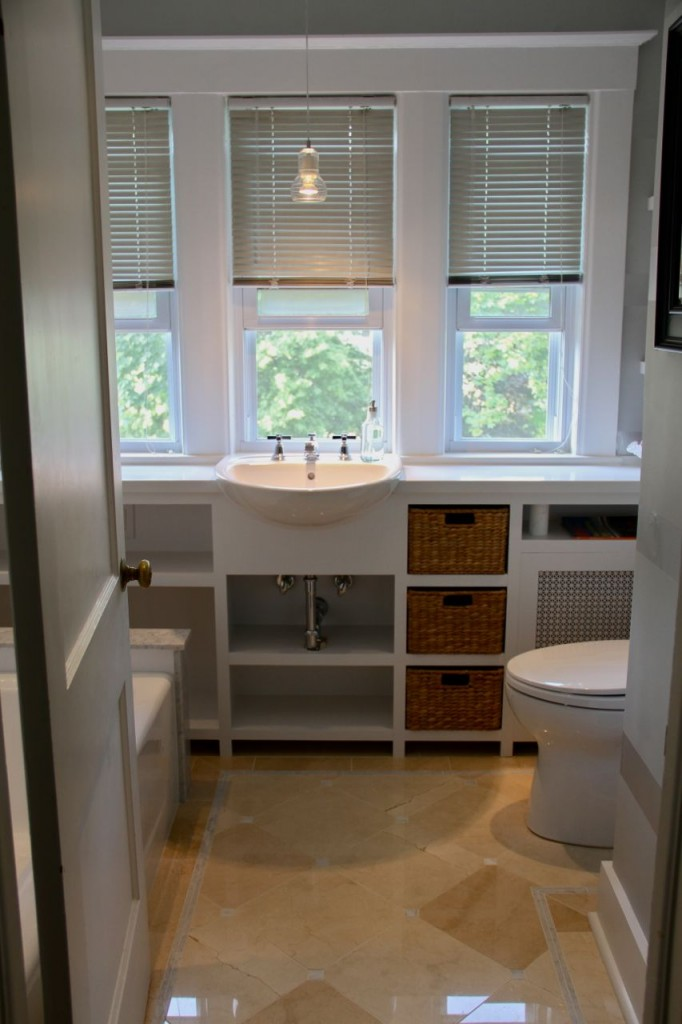 AFTER: Halogen recessed and pendant lighting illuminate the crema marfil marble floors, the white built-in cabinet, and the new, highly efficient toilet. So much better.