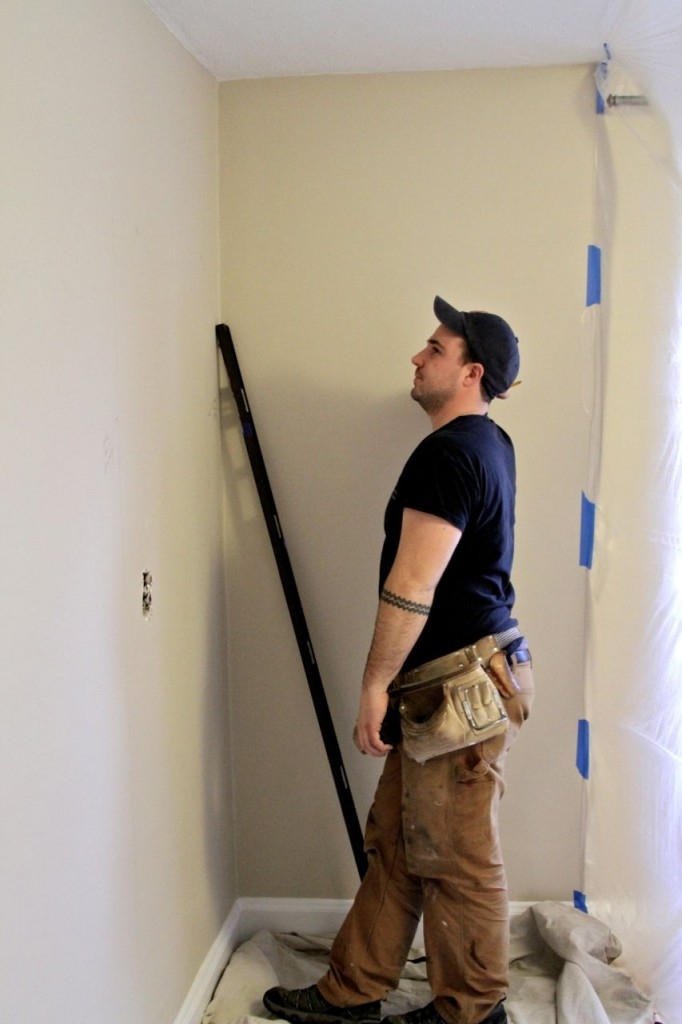 DURING: Dave, assessing the best place to make a hole for the soon-to-be-closet door.  This wall used to have a light switch for exterior lights. Yes, in the bedroom.