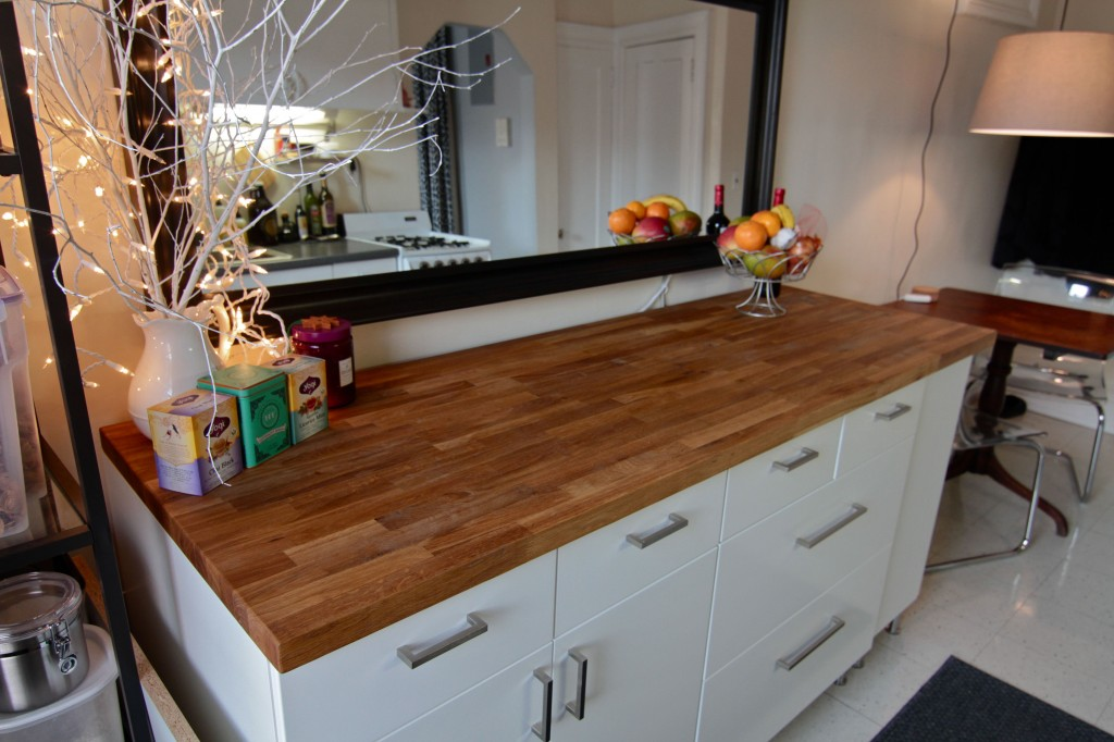 A six foot length of butcher block gives me the ability to spread out a little while cooking, but also has a warm and casual look. The cabinets are simply on feet, and are handy for our extra baking/cooking supplies.