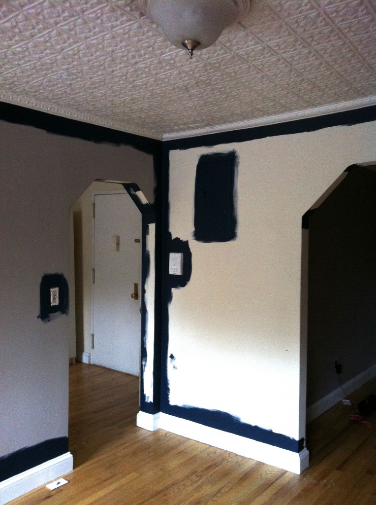 DURING: We wasted no time in taking a room that had three colors in it - light purply grey, charcoal, and buttercream - and unifying it with one solid, bold swath of paint.